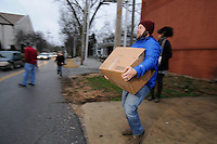 NWA Media/ J.T. Wampler - Chris Martin of Fayetteville carries a box of food to people lined up in cars Wednesday Dec. 24, 2014 in Bentonville. The Bentonville Kiwanis  Club distributed 540 boxes of food to area families Wednesday.