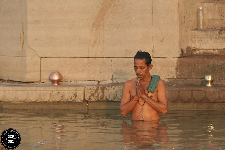 A Hindu pilgrim bathes in the water of the Ganges (Ganga) River and pauses to worship the morning sun and meditate.  For Hindus, the Ganges is the most sacred river in India.  Hindus believe that the Ganges purifies all those who bathe in her waters, cleansing them of all their sins.  Photograph by Douglas ZImmerman