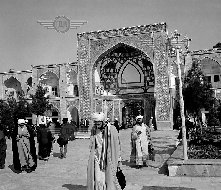 Shia clerics walking near the entrance of a madrasa.