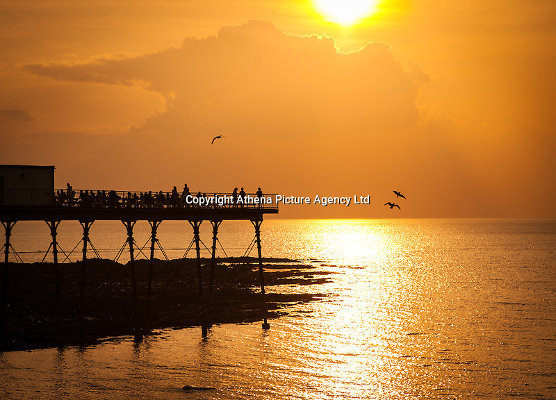 UK Weather: Aberystwyth, Ceredigion, West Wales <br />The sun goes down in the early evening over Aberystwyth Pier.