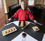 Scott Gilbert, general manager of the Luna Pizza, Pasta & Wings in O'Fallon. On the table: at left is a bruschetta duo, at center is eggplant parmesan, and at right is a scaled-down version of their house salad.