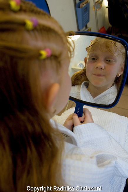 SAN ANTONIO, TEXAS-MARCH: Seven-year-old Ireland Buckley admires the braids she just had done at Spaaht, the kids-only spa at the Hyatt Regency Hill Country Resort March 25, 2005. The spa is one of a growing number across the U.S. catering to the teen and pre-teen age group and offering massages (40 USD), facials (40 USD), glitter manicures (30 USD), pedicures (35 USD) and hair braiding (3.50 USD/braid)(Photo by Radhika Chalasani)