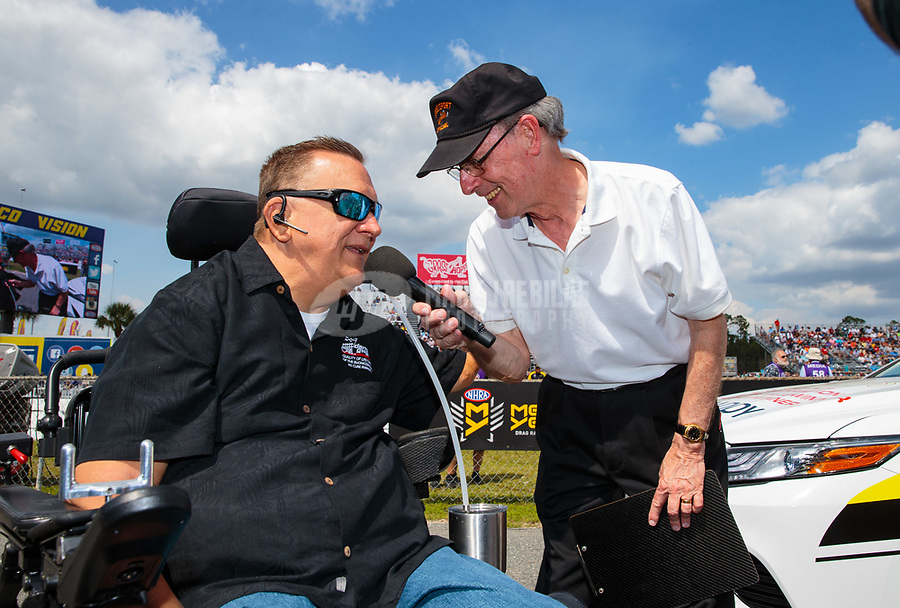"""Mar 15, 2019; Gainesville, FL, USA; NHRA driver Darrell Gwynn (left) is interviewed by announcer Bob Frey during the Toyota """"Unfinished Business"""" legends race at qualifying for the Gatornationals at Gainesville Raceway. Mandatory Credit: Mark J. Rebilas-USA TODAY Sports"""