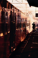 A man boards a train in Japan at sunset
