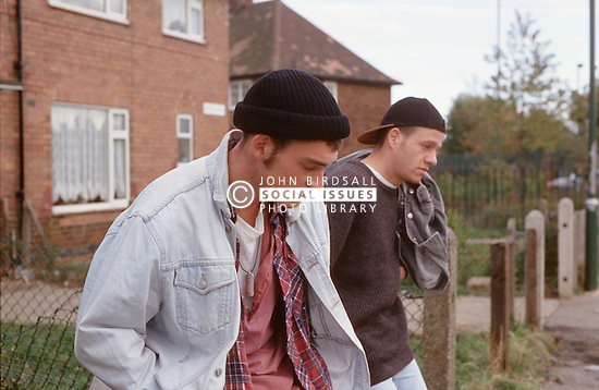 Two youths loitering on housing estate looking bored,