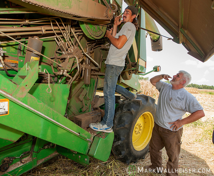 After suffering two consecutive days of break downs, Randy Dowdy watches worker Chevo Vargas and agonizes over a breakdown for the third day in the middle of harvesting his corn crop near Valdosta, Ga August 6, 2014.  Dowdy was able to repair with minimum down time today.