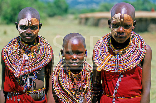Lolgorian, Kenya. Three Siria Maasai teenage girls with neck decorations and faces with white and red ochre paint.