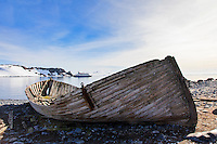 "A ruined boat, a relic of the Antarctic whaling era, frames the modern ship  ""Sea Spirit"" at Half Moon Island in the South Shetland Islands near the Antarctic peninsula."