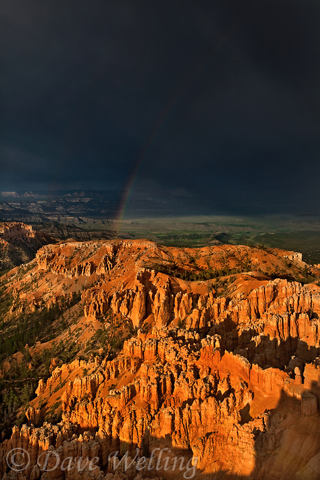 730750167 a rainbow forms over the hoodoos of bryce canyon national park during a summer monsoon rainstorm with ominous clouds in the background in this view from bryce point utah united states