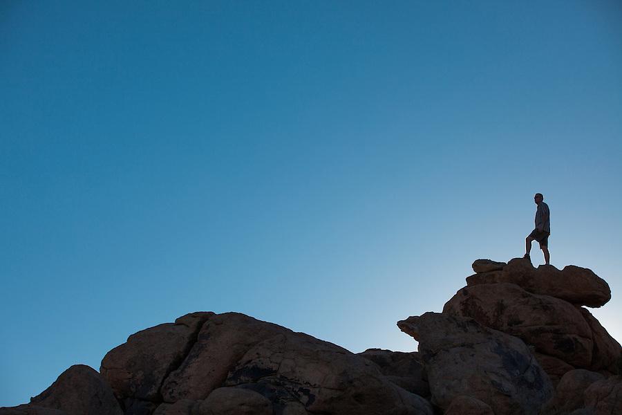 A backlit man in his 30's walks along a sandstone ridgeline in Joshua Tree National Park, California.
