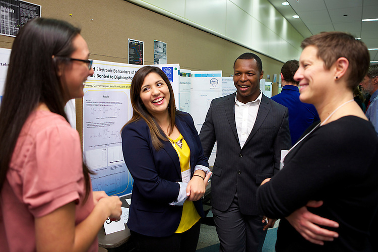 Stephanie Pachero (center left) and Joshua Smith present on their chemistry research on Palladium. DePaul University students presented posters of their own research at the College of Science and Health's 12th Annual Natural Science Mathematics and Technology Undergraduate Research Showcase November 7th, 2014 in the McGowan South science building on the Lincoln Park campus. (DePaul University/Jeff Carrion)