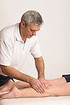 physiotherapist manipulates womans leg muscles
