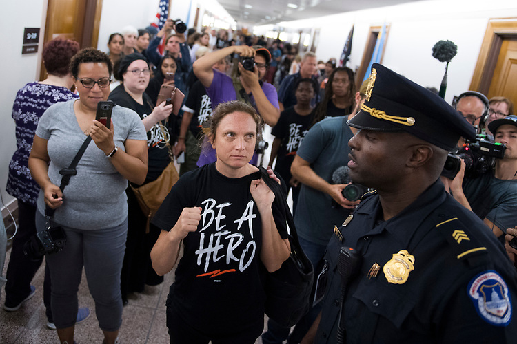 UNITED STATES - AUGUST 01: Jennifer Flynn Walker from the Center for Popular Democracy, talks with a Capitol Police officer during a protest to oppose Supreme Court nominee Brett Kavanaugh, outside the office of Sen. John Thune, R-S.D., in Dirksen Building on August 1, 2018. (Photo By Tom Williams/CQ Roll Call)