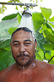 FRENCH POLYNESIA, Moorea. Portrait of man showering outside after swimming in the ocean.