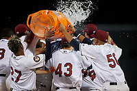 Mahoning Valley Scrappers Pedro Alfonseca (27) and Jonathan Lopez (50) dump the water cooler on Michael Cooper (4) while being mobbed by teammates after hitting a walk off single during a NY-Penn League game against the Hudson Valley Renegades on July 15, 2019 at Eastwood Field in Niles, Ohio.  Mahoning Valley defeated Hudson Valley 6-5.  (Mike Janes/Four Seam Images)