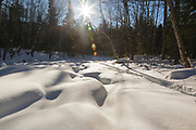 Snowshoeing along Franconia Brook in Lincoln, New Hampshire during the winter months.