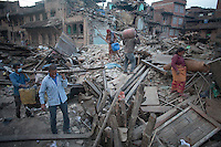 Nepali people carry their belongings through  collapsed houses at Vaktapur, outskirt of Kathmandu, Nepal. May 1, 2015