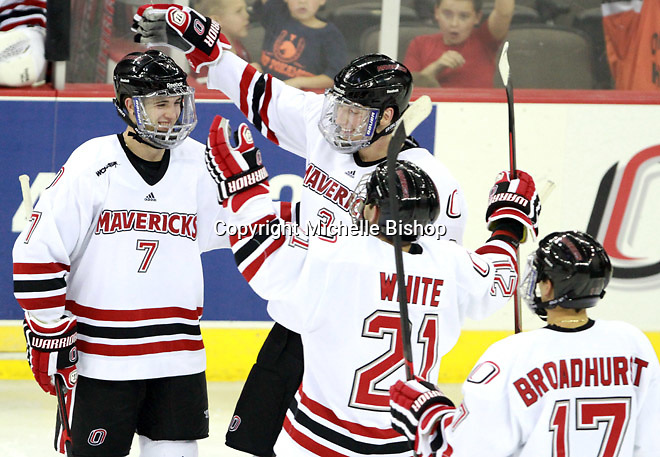 Nebraska-Omaha's Michael Young (7) is congratulated by teammates Andrej Sustr (3), Matt White and Terry Broadhurst after scoring in the second period. (Photo by Michelle Bishop) .
