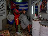 HAVANA, CUBA - JUNE 15: Cuban hair dresser Adoni Sanabria, cuts the hair of customer Yaikel Lopez, in Old Havana, Habana Vieja on June 15, 2015 in Havana, Cuba. <br /> Daniel Berehulak for Panasonic/Lumix