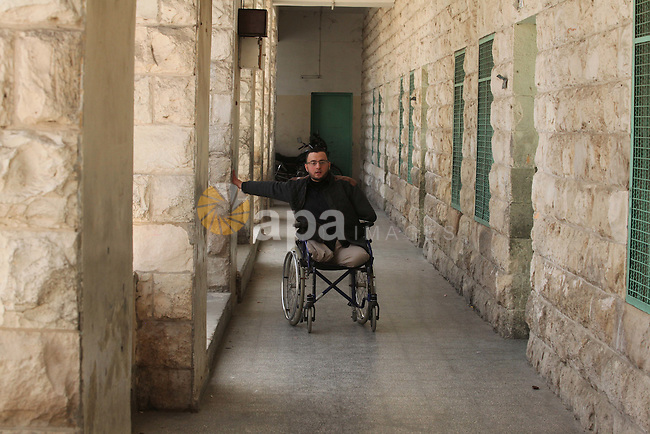 Wheelchair-bound Palestinian student teacher Ahmed al-Sawaferi, 25, who said that he lost his both legs and his left arm in an Israeli air strike in 2008, pushes himself at an elementary school in Gaza City March 19, 2015. Al-Sawaferi, a father for two children, is due to hold a B.A in Islamic studies after finishing his last university semester in June this year. Photo by Ashraf Amra