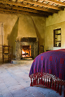 This rustic bedroom is simply furnished and heated with a large open fireplace