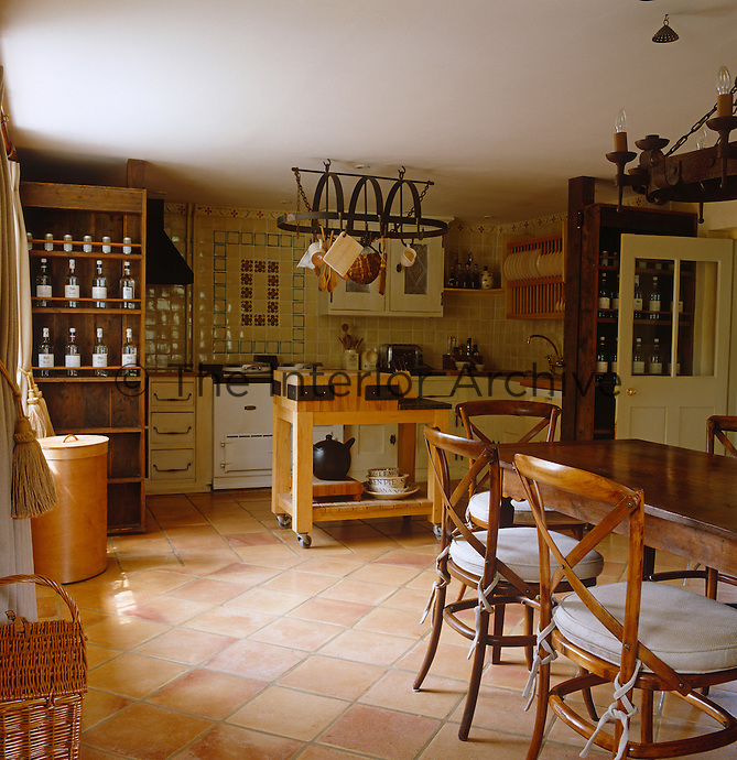 A spacious country kitchen/dining room has a white Aga and a Mediterranean-style terracotta tiled floor