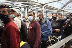 Palestinian labourers wear masks queue to enter Israel through the Mitar checkpoint in the West Bank city of Hebron on June 28, 2020. Photo by Mosab Shawer