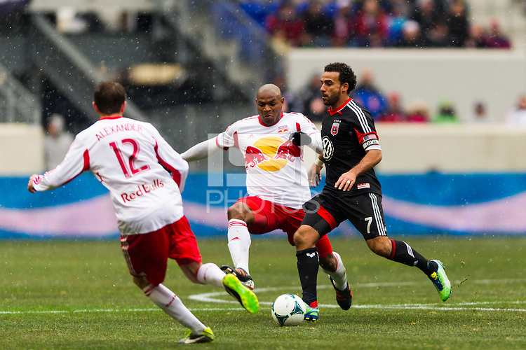 Dwayne De Rosario (7) of D. C. United is defended by Jamison Olave (4) and Eric Alexander (12) of the New York Red Bulls. The New York Red Bulls and D. C. United played to a 0-0 tie during a Major League Soccer (MLS) match at Red Bull Arena in Harrison, NJ, on March 16, 2013.