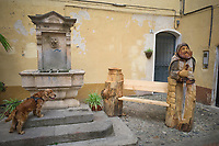 Italy. Liguria Region. Ospedaletti. An old fountain in the town center. Shake is a Cocker Spaniel which is a breed of gun dog. A wooden sculpture of a bench with a old medieval military defense tower and a man dressed to depart to the Crusades.The Crusades were a series of religious wars initiated, supported, and sometimes directed by the Latin Church in the medieval period. The term refers especially to the Eastern Mediterranean campaigns in the period between 1096 and 1271 that had the objective of recovering the Holy Land from Islamic rule. 21.07.2020 © 2020 Didier Ruef