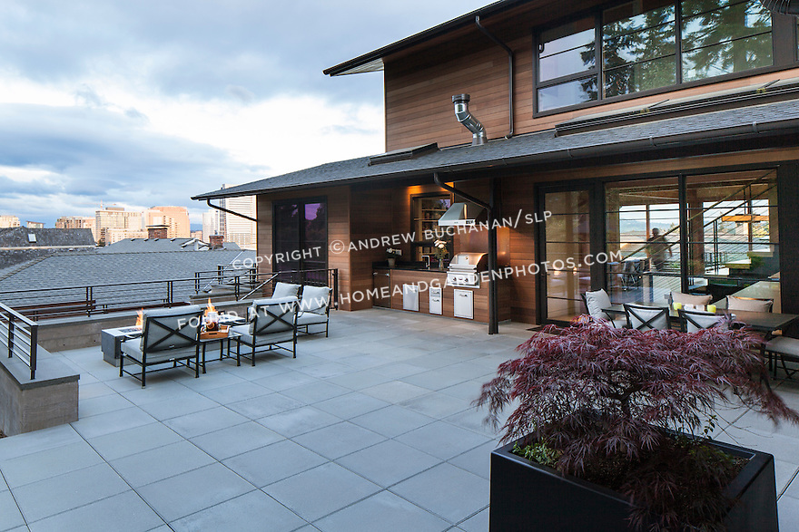 Patio area with outdoor dining table and firepit with Bellevue skyline in the background.