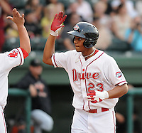 Infielder Xander Bogaerts (23) of the Greenville Drive is congratulated after hitting a home run in a game against the Augusta GreenJackets on August 27, 2011, at Fluor Field at the West End in Greenville, South Carolina. Greenville defeated Augusta, 10-4. (Tom Priddy/Four Seam Images)