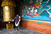 A Bhutanese man turns the prayer wheel inside the Punakha Dzong in Punakha, the older capital of Bhutan. Punakha is the administrative centre of Punakha dzongkhag, one of the 20 districts of Bhutan. Photo: Sanjit Das/Panos