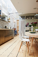 The kitchen is an impressive, open-plan space incorporating a dining table and chairs. The kitchen cupboards are custom-built by Bert & May and an exposed brick façade, painted to look old, adds an industrial vibe to the kitchen. The kitchen chairs are Eames DSW