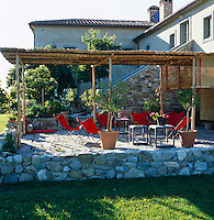 A rustic loggia provides shade on the stone terrace which is furnished with bright red chairs