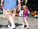 FATHER HOLDS HAND of SMALL CHILD as THEY WALK ALONG TOURISTS AREA