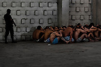 "Mara gang members, having hands behind theirs heads and sitting on the floor, pass through a random search at the detention center in San Salvador, El Salvador, 20 February 2014. Although the country's two major gangs reached a truce in 2012, the police holding cells currently house more than 3000 inmates, five times more than the official built capacity. Partly because the ordinary Mara gang members did not break with their criminal activities (extortion, street-level distribution of drugs, etc.), partly because Salvadorean police still applies controversial anti-gang law which allows to detain almost anyone for ""suspicion of gang membership"". Accused young men are held in police detention centers where up to 25 inmates may share a cell of five-by-five metres. Here, in the dark overcrowded cages, under harsh and life-threatening conditions, suspected gang members wait long months, sometimes years, for trial or for to be transported to a regular prison."