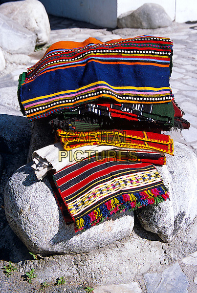 Colourful blankets on display on rocks outside gift and craft shop, Bansko, Bulgaria