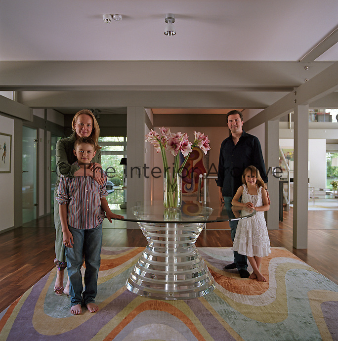 Anna Belayeva, her husband Michael Schmidt and their two children stand beside the glass table in the main hall of their home
