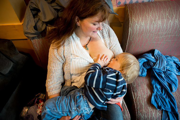 A woman breastfeeds her two year old toddler in a coffee shop.<br /> <br /> Image from the &quot;We Do It In Public&quot; documentary photography project collection: <br />  www.breastfeedinginpublic.co.uk<br /> <br /> Dorset, England, UK<br /> 17/04/2013