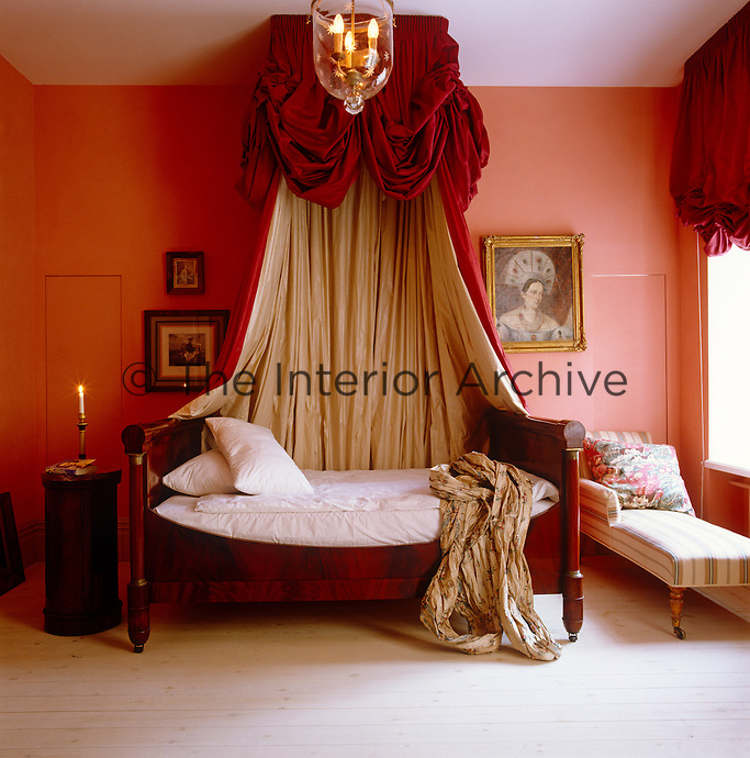 In a bedroom of Napoleonic splendour blood-red velvet bed curtains glow against coral-pink walls