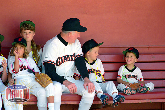 SAN FRANCISCO, CA - Manager Roger Craig of the San Francisco Giants sits in the dugout with little kids before a game at Candlestick Park in San Francisco, California in 1989. Photo by Brad Mangin