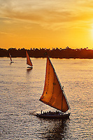 Three falukas with sightseers on Nile River at sunset, modern day Luxor, or ancient Thebes