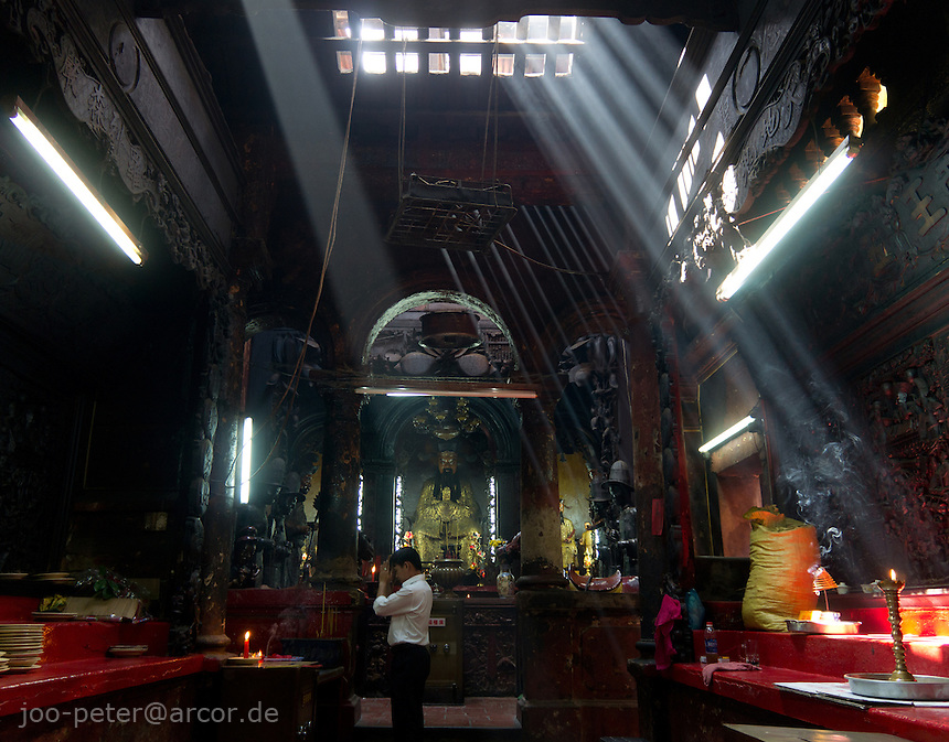 sunbeams enligthen Chua Ngoc Hoang temple while a man is praying,  in Ho Chi Minh City / Saigon,  Vietnam. Taoist temple Phouc Hai Tu (turtle sanctuary) is called Cua Ngoc Hoang (Jade emperor) by the peope. Vietnamese belief is a blend of Buddhism, Taoism and animism