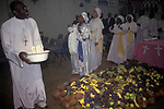 "The Celestial Church of Christ. A baby naming ceremony. The child is being held by a ""spirit medium"", as members of the congregation dance around the huge pile of fruit. She will after this ceremony see into the child's future speaking in tongues, the father records hers words while a scribe translates them. 1990s London UK"