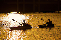 Couple kayaking on Lady Bird Lake during sunset, golden hour, in Austin, Texas. Summer recreational pursuit.