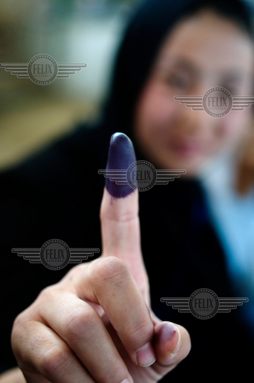 A young woman shows her ink-stained finger that proves she's voted, and stops her voting twice, during the 2009 Afghan elections....