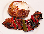 Teriaki steak, with peppers and onions, and a baked potato with butter lay on a white plate.