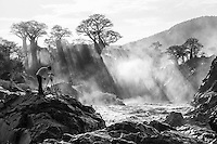 A landscape photographer, my friend Johan, at work at the spectacular Epupa Falls in Namibia one glorious morning in February with the falls in flood after the recent rains.