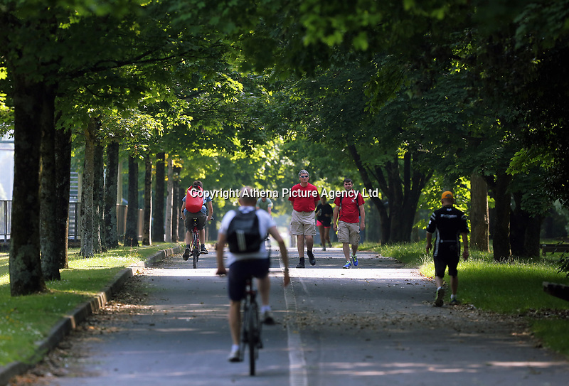 WEATHER PICTURE WALES<br />Pictured: Cyclists ride along walkers on the Oystermouth Road path in Swansea Bay, Wales, UK. Wednesday 21 June 2017<br />Re: A prolonged period of sunshine and high temperatures has caused one of the longest heatwaves in the UK.