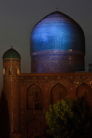 Detail of the Tilla-Kari (Gold-covered) madrasah, 17th century, on the Registan square, Samarkand, Uzbekistan, showing small cylindrical corner towers crowned by cupolas and the huge monochrome blue dome, on July 16, 2010 at dusk. Samarkand, a city on the Silk Road, founded as Afrosiab in the 7th century BC, is a meeting point for the world's cultures. Its most important development was in the Timurid period, 14th to 15th centuries.